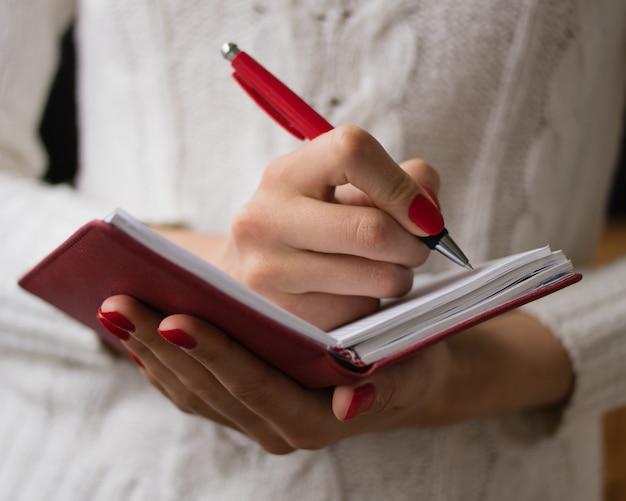 Mãos femininas, escrita, em, um, caderno