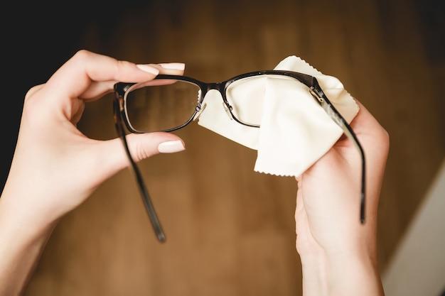 Mãos femininas esfregando óculos de aro preto com esponja especial