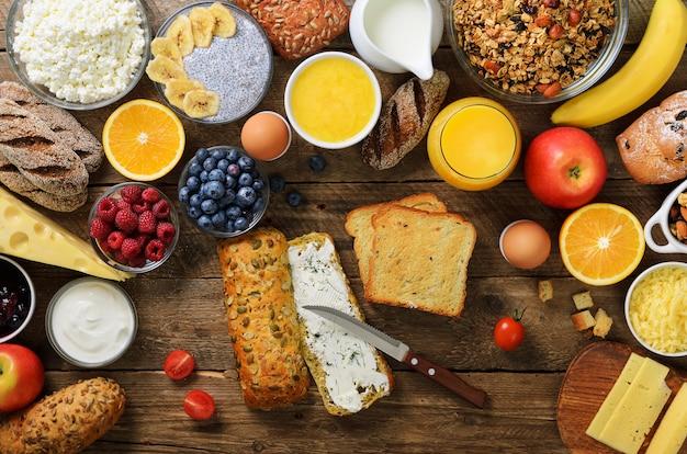 Mãos femininas espalhar manteiga no pão. mulher cozinhando o café da manhã. ingredientes de pequeno-almoço saudável, quadro de comida.
