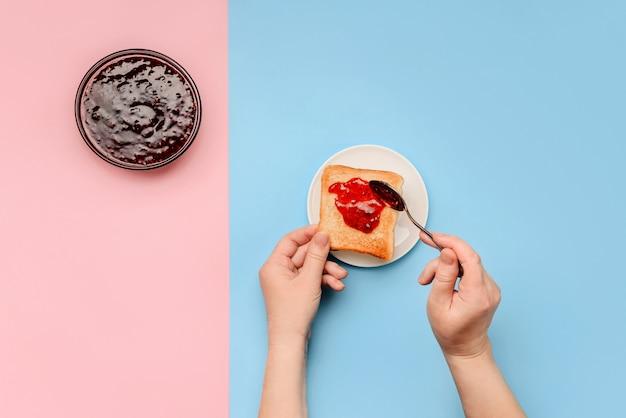 Mãos femininas espalhar torrada de pão com geléia ao lado de um prato de geléia em uma parede rosa e azul com um espaço de cópia.