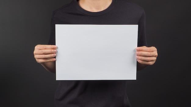 Mãos femininas está segurando o papel a4 em branco sobre fundo preto.