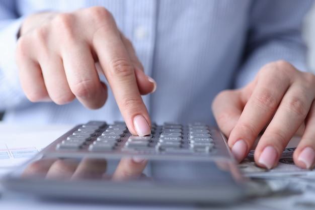Mãos femininas estão contando com calculadora na mesa closeup