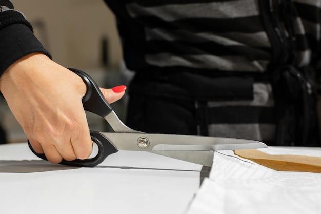 Mãos femininas estão cortando o tecido com uma tesoura de alfaiate no padrão de papel