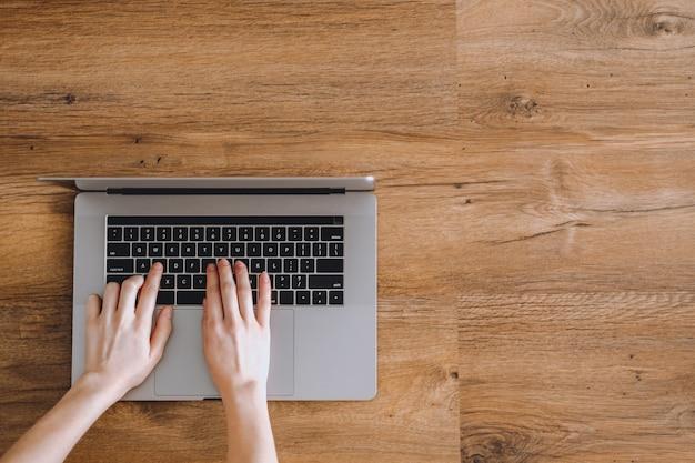 Mãos femininas estão digitando em um teclado de notebook em um fundo de madeira