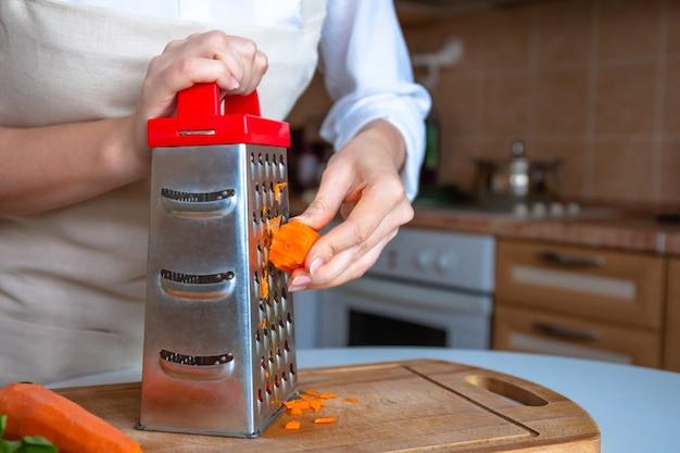 Mãos femininas estão esfregando cenouras frescas de laranja em um ralador de prata de aço.