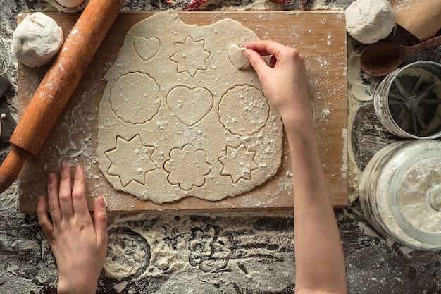 Mãos femininas estão fazendo biscoitos em forma de massa na placa de madeira