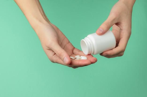 Mãos femininas estão segurando o frasco de comprimidos brancos e comprimidos sobre fundo azul. saúde. doença.