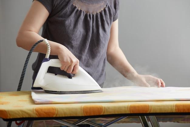 Mãos femininas estão segurando um ferro branco e ferro sobre uma tábua de passar. fechar-se. sem rosto. copie o espaço em fundo cinza. deveres domésticos e atendimento domiciliar.