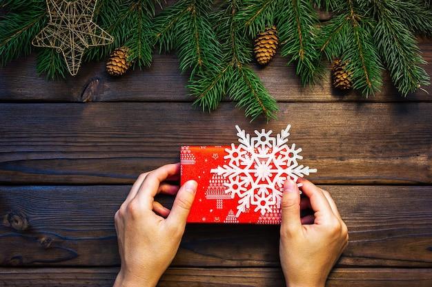 Mãos femininas estão segurando um presente de natal vermelho sobre um fundo escuro de madeira, há um floco de neve branco ...