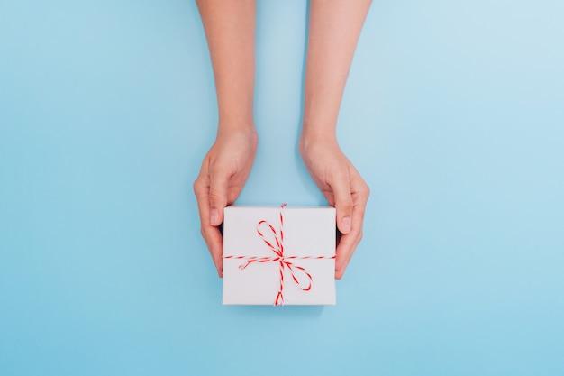 Mãos femininas estão segurando uma caixa de presente branca com uma fita fina como um presente para o natal, ano novo, dia das mães ou aniversário em um fundo azul tabela, vista superior. lugar para texto.