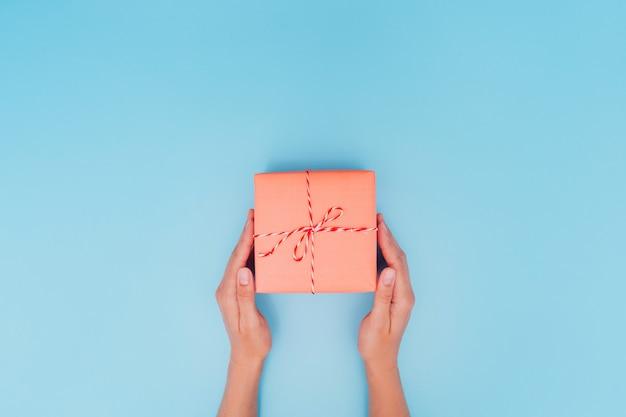 Mãos femininas estão segurando uma caixa de presente rosa com uma fita fina como um presente para o natal, ano novo, dia das mães ou aniversário em um fundo azul tabela, vista superior. lugar para texto.