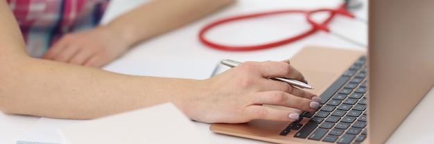 Mãos femininas estão trabalhando no laptop ao lado do estetoscópio.