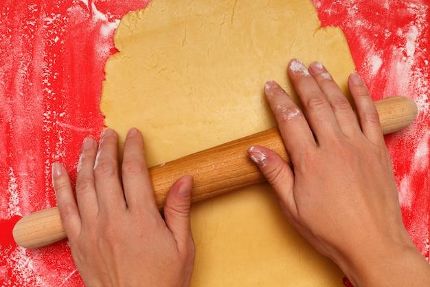 Mãos femininas estendem a massa para biscoitos de natal