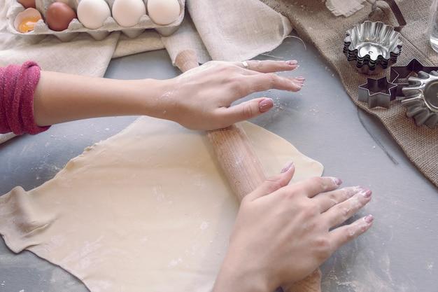 Mãos femininas estendem a massa