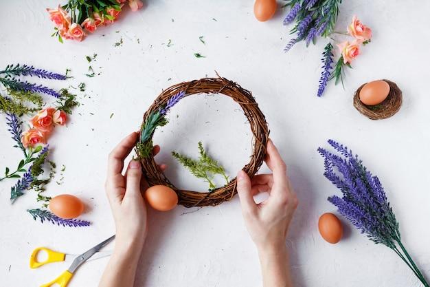 Mãos femininas fazem guirlanda de páscoa de flores, ervas e ovos em cinza