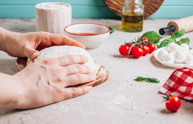 Mãos femininas fazem pizza, os ingredientes para uma pizza caseira de margherita na superfície da pedra