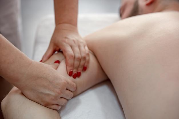 Mãos femininas fazem uma massagem terapêutica do corpo para um homem no salão.