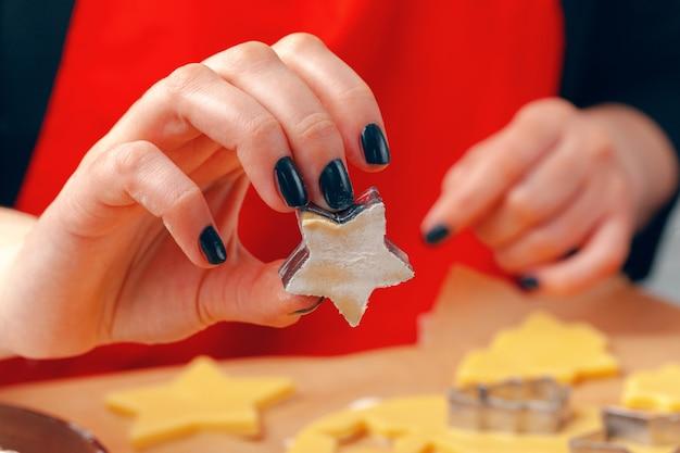 Mãos femininas fazendo biscoitos de massa fresca em casa