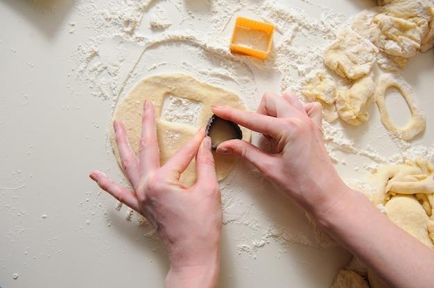 Mãos femininas fazendo biscoitos de massa fresca