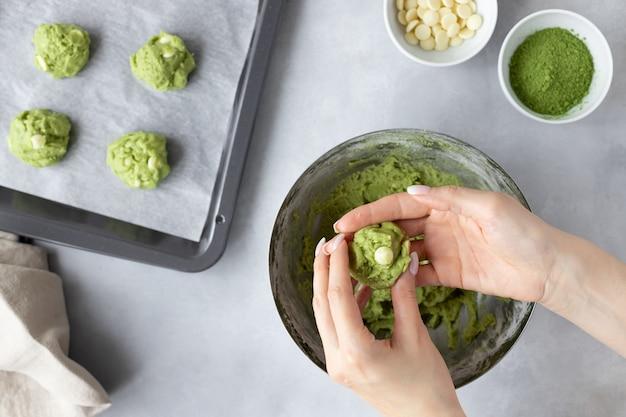 Mãos femininas fazendo bolinho de chá verde matcha