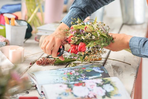 Mãos femininas fazendo buquê de flores diferentes