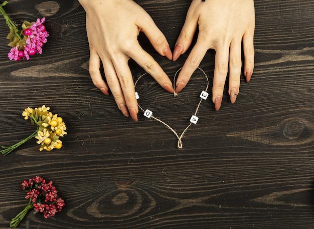 Mãos femininas fazendo formato de coração de linha em fundo de madeira.