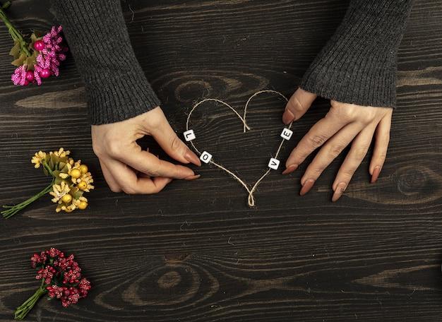 Mãos femininas fazendo formato de coração de linha na mesa de madeira.
