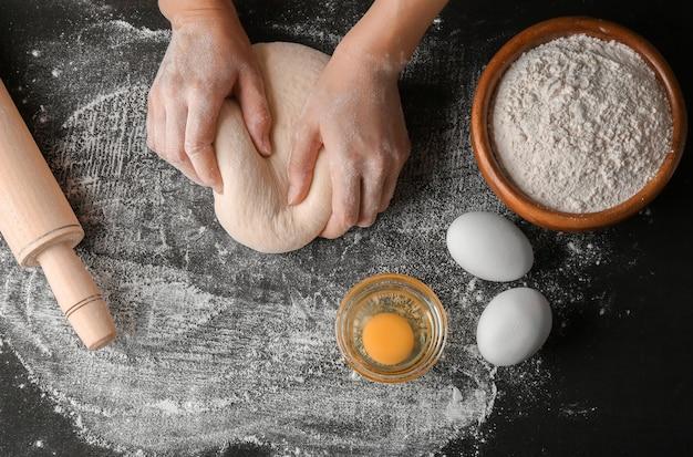 Mãos femininas fazendo massa para pizza na mesa preta