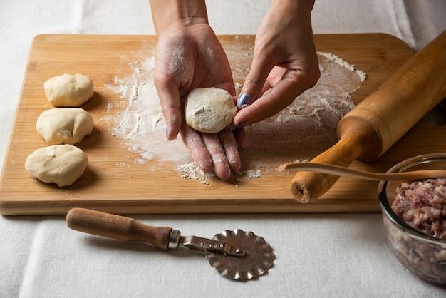 Mãos femininas fazendo preparação para o gutab de prato do azerbaijão.