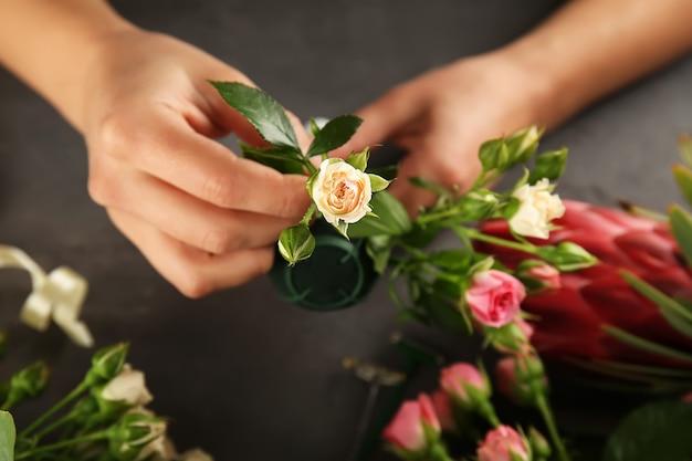 Mãos femininas fazendo um lindo buquê de flores na superfície escura