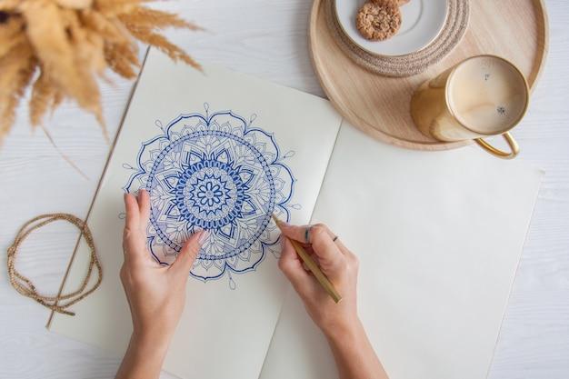 Mãos femininas fecham desenhar mandala floral redonda decorativa. hobby e relaxamento em casa. uma caneca de café e biscoitos em uma bandeja de madeira. fundo branco.