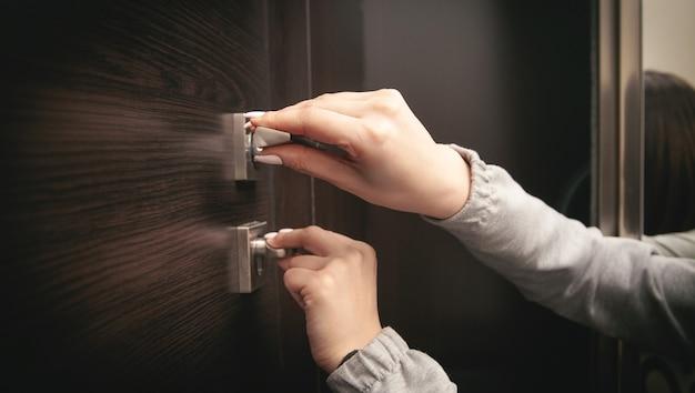 Mãos femininas fecharam uma porta em casa.