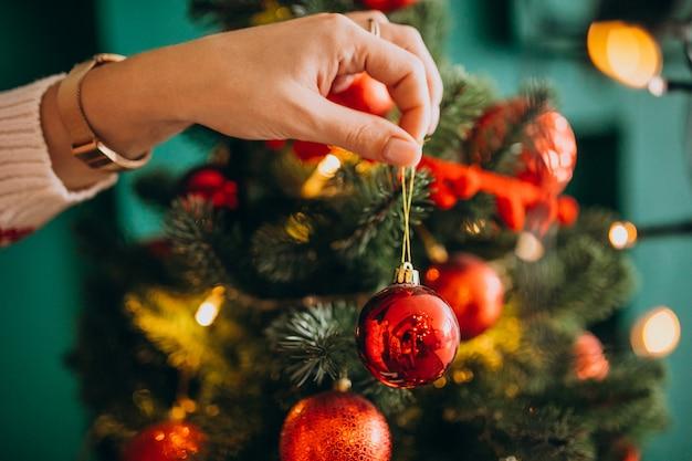 Mãos femininas fechem, decorando a árvore de natal com bolas vermelhas
