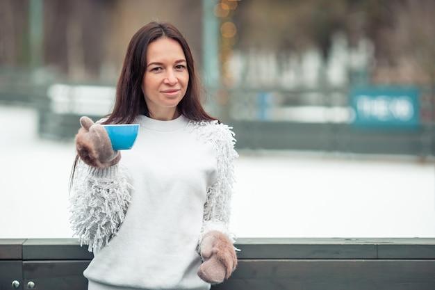 Mãos femininas holdink branco xícara de café com marshmallows brancos e rosa