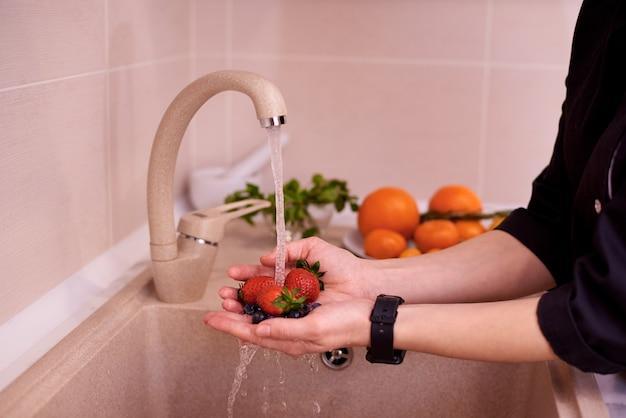 Mãos femininas lavam morangos e mirtilos sob um fluxo de água em uma pia na cozinha.