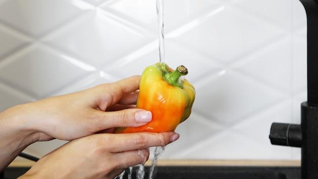 Mãos femininas lavando pimenta de cor amarela e vermelha. fundo branco de cozinha