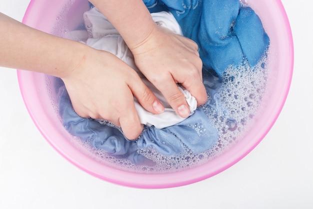 Mãos femininas lavando roupas brancas e azuis com espuma na bacia, vista superior