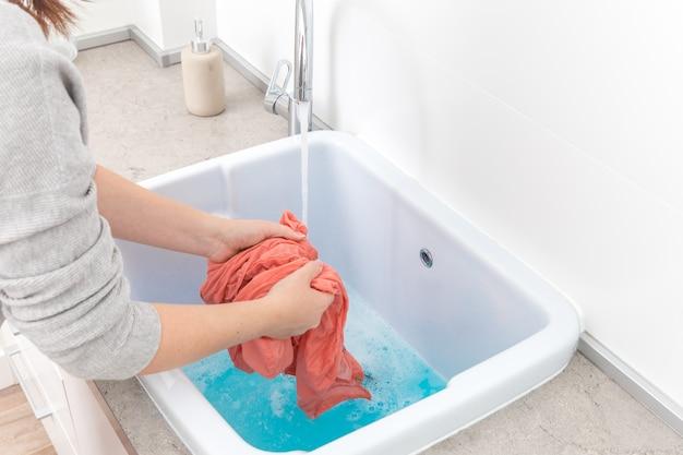 Mãos femininas lavando roupas de cor na pia