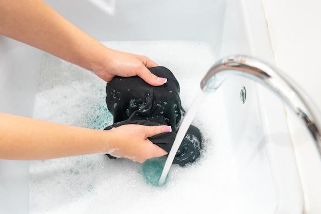 Mãos femininas lavando roupas pretas na bacia