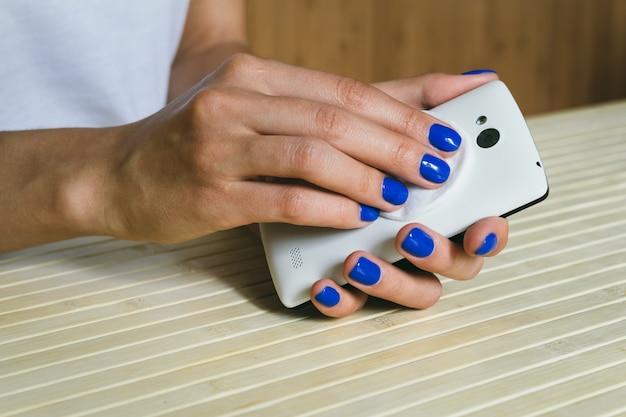 Mãos femininas limpas de poeira e sujeira celular da cor branca
