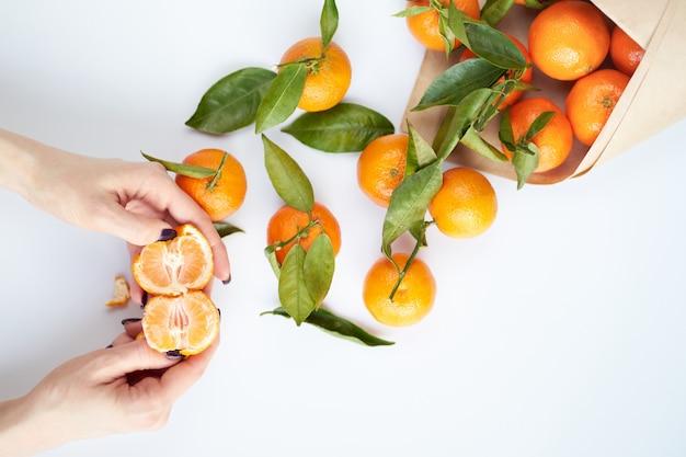 Mãos femininas limpeza tangerina. as tangerinas frescas alaranjadas com folhas verdes encontram-se em uma superfície branca