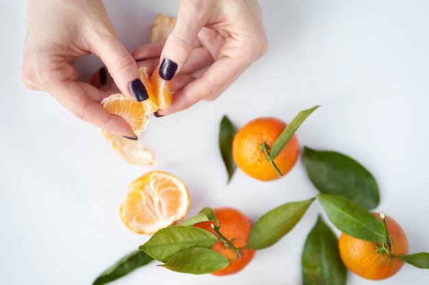 Mãos femininas limpeza tangerina. as tangerinas frescas alaranjadas com folhas verdes encontram-se.