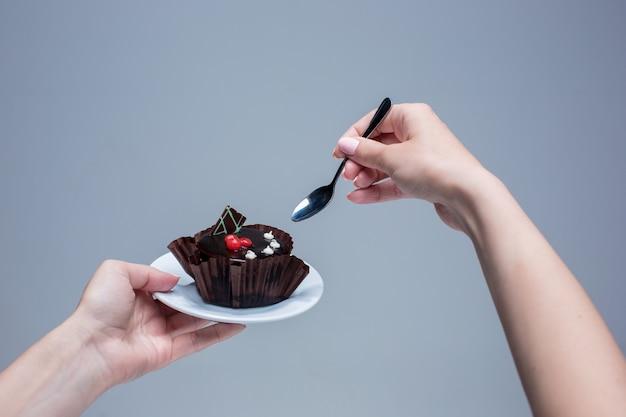 Mãos femininas, mantendo o bolo com a colher em cinza