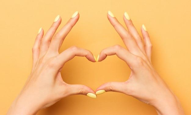 Mãos femininas mostram um símbolo do coração isolado.