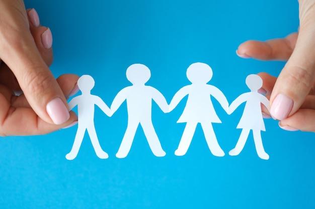 Mãos femininas mostrando família de figuras de papel, família e conceito de bem-estar