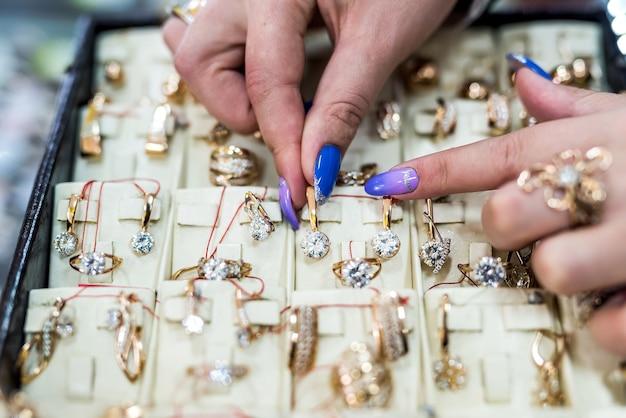 Mãos femininas mostrando joias de ouro na loja