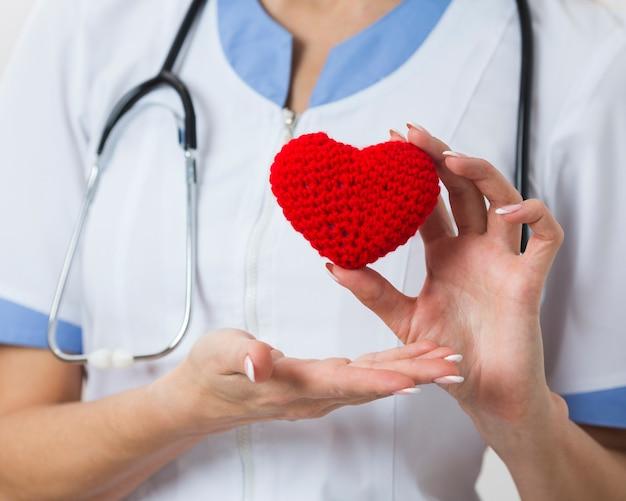 Mãos femininas, mostrando um coração de pelúcia