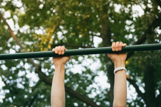 Mãos femininas na barra horizontal ao ar livre no parque