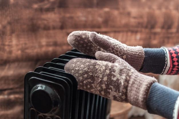 Mãos femininas no natal, luvas quentes de inverno no aquecedor. mantenha quente no inverno, nas noites frias. estação de aquecimento