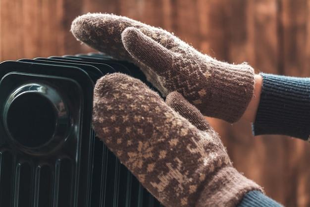 Mãos femininas no natal, luvas quentes de inverno no aquecedor. mantenha quente no inverno, noites frias